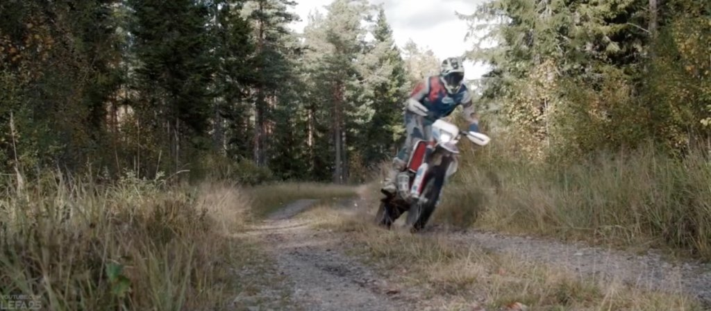 フラットダートでバイクが手前に土煙をあげながら横切っていくシーン