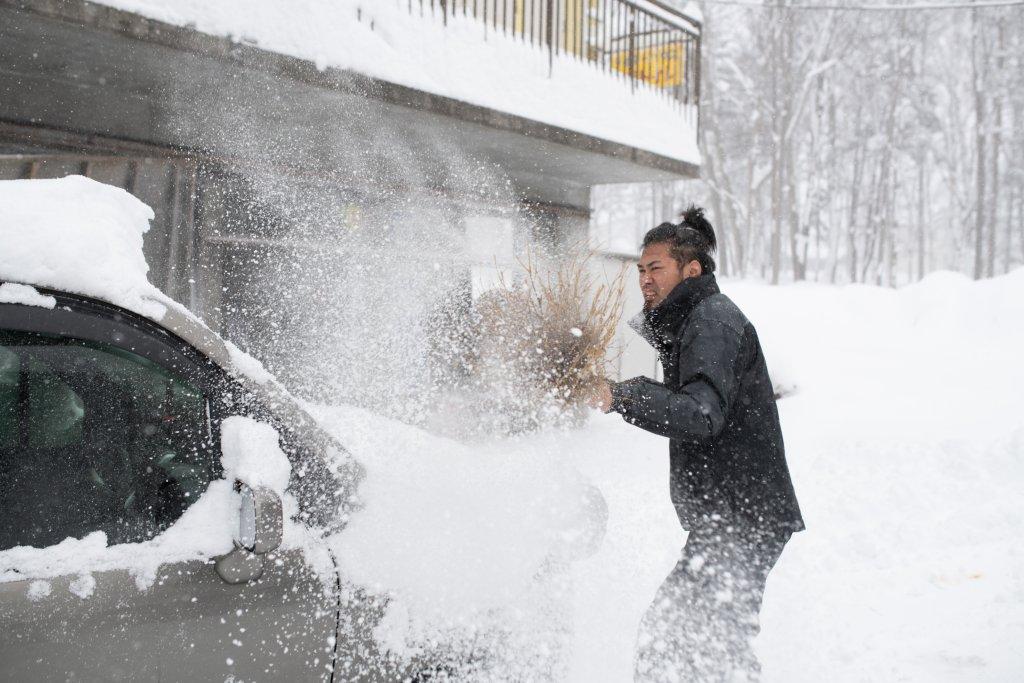 サポートカーの雪を払うイケダさん